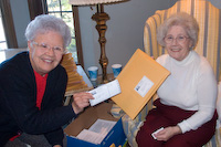 Loretta and Norma labeling envelopes